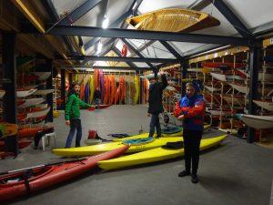 Een botenhuis vol verschillende types kayaks en canadezen.